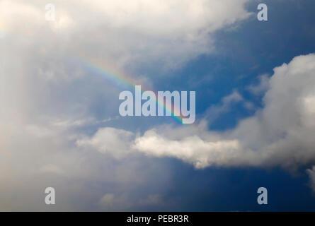 Natürliche Hintergrund mit einem hellen bunten Regenbogen unter weissen flauschigen Wolken vor blauem Himmel nach einem Regen im Sommer - Stockfoto