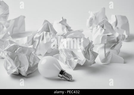 Nahaufnahme der Energieeinsparung Lampe mit Zerknüllten Papiere auf Weiß - Stockfoto