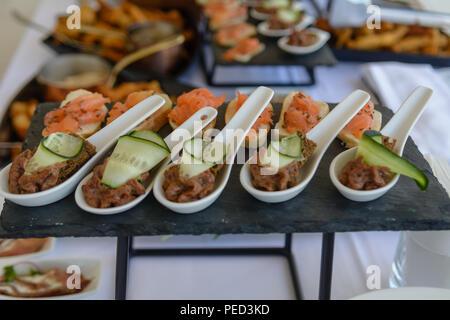 Lecker Thunfisch Pastete aus weisser Keramik Löffel mit Gurke deko Stein Platte mit Lachs im Hintergrund serviert. - Stockfoto