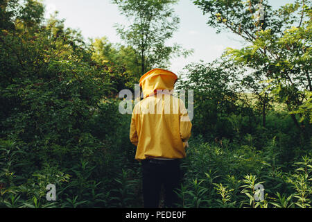 Von der Rückseite des Imkers mit Schutzanzug zu Fuß in die Natur zu seinem Bienenhaus Schuß - Stockfoto