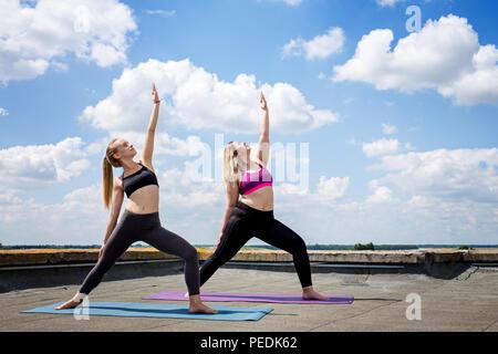 Zwei junge Frauen, die Yoga machen - Stockfoto