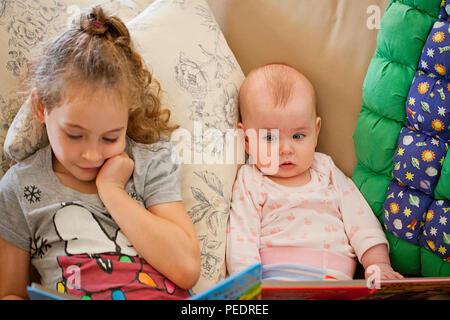 Junge Mädchen das Lesen zu einem Baby girl - Stockfoto