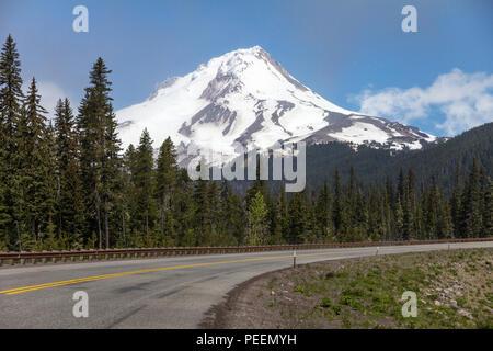 Highway 35 in Oregon Kurven im Vordergrund, wie es vergeht eine ungehinderte Sicht auf Gletscher, schneebedeckten Mount Hood und die Wälder unterhalb. - Stockfoto