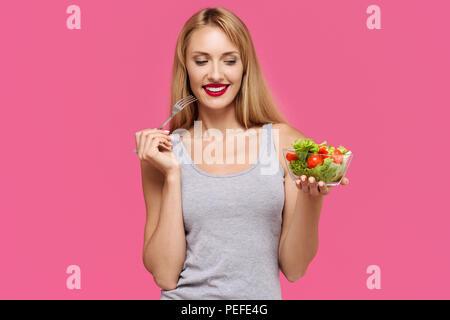 Junge schöne Mädchen mit auf einem rosa Hintergrund hält Gemüsesalat und Gabel in den Händen. Konzept der gesunden Ernährung - Stockfoto