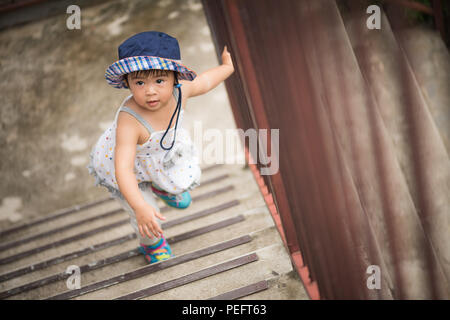 Glückliche kleine süße Mädchen zu Fuß die Treppe hinauf. Kid erster Schritt Konzept. - Stockfoto