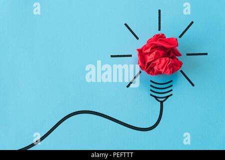 Inspiration und tolle Idee Konzept. Lampe mit zerknittertem Papier gelb auf blauem Hintergrund. - Stockfoto