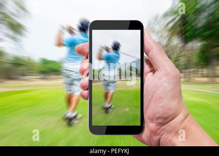 Mit der Kamera im Smartphone Aufnehmen von Fotos und Videos aufzeichnen, wenn andere Schwingen auf Golf abzweigenden Boden. - Stockfoto