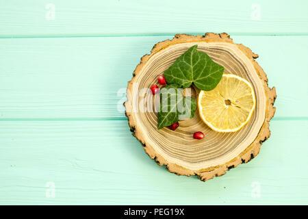 Holz mit mit Zitronenscheiben und Granatapfel Beeren auf einem türkisen Hintergrund - Stockfoto