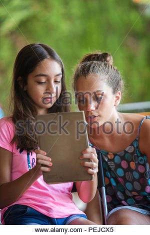 Zwei junge Mädchen Spaß und Spielen mit einem Tablet - Stockfoto