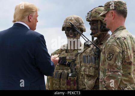 Us-Präsident Donald Trump ist ein 10 Combat Aviation Brigade Herausforderung Münze nach einem Luftangriff und Gun regen Demonstration bei einem Besuch der John McCain National Defense Authorization Act, den 13. August in Fort Drum, New York 2018 zu unterzeichnen. - Stockfoto