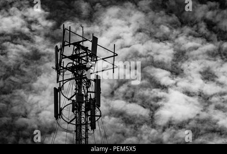 Schwarz-weiß Bild von Telekommunikation Turm gegen den grauen Himmel und weißen Wolken. Antenne am dunklen Himmel Hintergrund. Radio und Sat-Pol. Commun - Stockfoto