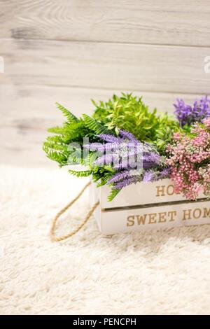 Blumen in einem weißen Holzkiste. Inneneinrichtung, Interieur Komposition. Blumen und Zweige in einer Holzkiste auf weißem Holz- Hintergrund - Stockfoto