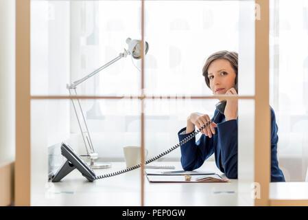 Unternehmerin oder Managerin sprechen auf einem Telefon im Büro in die Kamera durch eine Glaswand mit einem ernsten Ausdruck. - Stockfoto