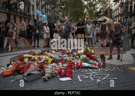 Barcelona, Spanien. 16. August 2018. Eine Frau stellt eine Kerze auf dem Boden von Las Ramblas in Barcelona erinnert an die Opfer der Terroranschläge im vergangenen Jahr zahlen, tötete 16 Menschen und verletzt mehr als 120 Wenn zwei Fahrzeuge in die Massen gestuerzt. Credit: Jordi Boixareu/Alamy leben Nachrichten - Stockfoto