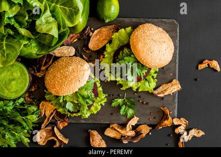 Vegane Burger mit Zuckerrüben Schnitzel und grüne Smoothies auf schwarzem Hintergrund. Gesund Vegan essen. Detox Diät. - Stockfoto