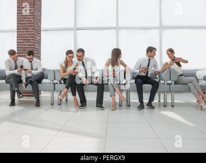 Gruppe der Mitarbeiter mit Smartphones beim Sitzen im Büro Lobby - Stockfoto