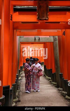 KYOTO, Japan - 28. NOVEMBER 2016: Kimono kostümierte Frauen besuchen Fushimi Inari Taisha Shrine in Kyoto, Japan. Es gibt mehr als 10.000 torii Gates in F - Stockfoto