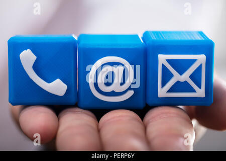 Nahaufnahme einer Hand Holding blau würfelförmige Blöcke mit verschiedenen Kontaktoptionen - Stockfoto