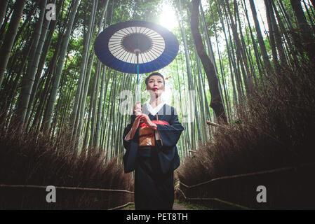 Schönen japanischen ältere Frau zu Fuß im Bambuswald - Stockfoto