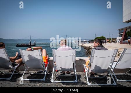Touristen und Einheimische restant und ein Sonnenbad an der Waterfront in Lissabon, Portugal. - Stockfoto
