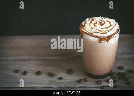 Kalte frappe Kaffee (frappuccino) mit Sahne und Karamell auf dunklem Hintergrund, kopieren. - Stockfoto