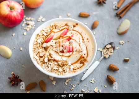 Apple Pie Smoothie Schüssel. Frühstück smoothie Schale mit Äpfeln, Zimt, Mandelmilch, Hafer Müsli, gesalzen Karamell und Gewürze, Ansicht von oben. - Stockfoto