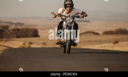 Porträt der jungen Mann, der ein Motorrad schnell auf der Autobahn. Männliche Fahrer nach vorne während der Fahrt sein Motorrad. - Stockfoto