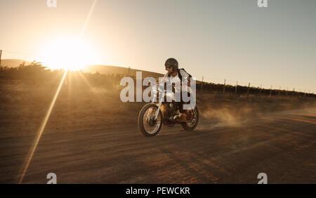 Männliche Biker fahren Oldtimer Motorrad auf der Piste. Mann, schnell mit dem Fahrrad auf der Landstraße. - Stockfoto