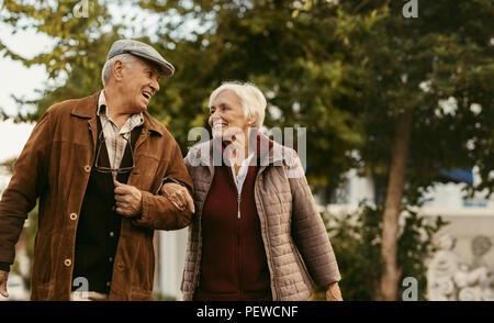 Portrait von Happy pensionierter Mann und Frau in warme Kleidung Wandern draußen auf der Straße. Liebevolle senior Paar genießen einen Spaziergang an einem Wintertag. - Stockfoto