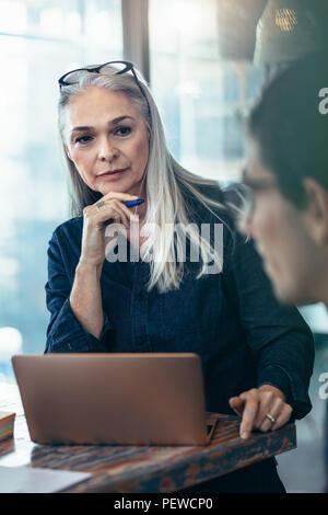 Senior Business Frau hören auf ihre männlichen Kollegen während der Sitzung im Büro. Reife Frauen die Aufmerksamkeit auf die Diskussion in der Sitzung. - Stockfoto