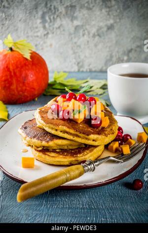 Herbstliches frühstück Idee, Kürbis Pfannkuchen, mit Scheiben von Kürbis, Ahornsirup oder Honig, Moosbeere, auf einem blauen konkreten Hintergrund, Platz für Text - Stockfoto