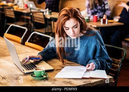 Junge Frau mit langen roten Haaren sitzen am Tisch, Arbeiten am Laptop. - Stockfoto