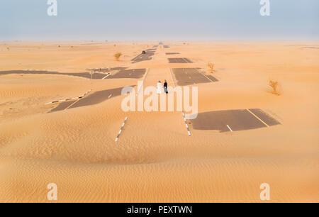 Emiratische Paar in einer Wüste im Sand bedeckt Straße suchen - Stockfoto