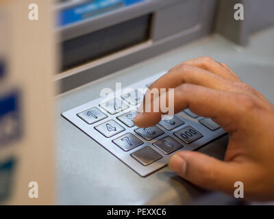 Die Person, die das Passwort einzugeben, wenn das Geld von der Bank abheben - Stockfoto