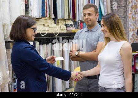 Weibliche store Eigentümer gibt Visitenkarte auf ein junges Paar. Small Business home Textil shop - Stockfoto