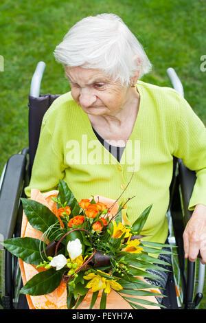Behinderte ältere Frau sitzt im Rollstuhl, ein Blumenstrauß zum Geburtstag - Stockfoto