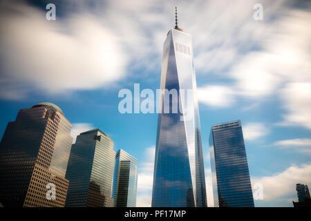 Sich schnell bewegende Wolken über einem WTC und das Denkmal 9/11 in Lower Manhattan, New York City. - Stockfoto