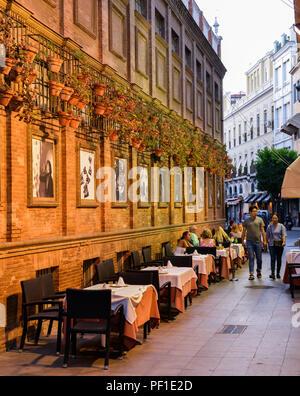 Sevilla, Spanien - 15. Juli 2018: Romantisch im Freien spanisches Restaurant mit Blumentöpfe auf wand Im Herzen der Altstadt - Stockfoto
