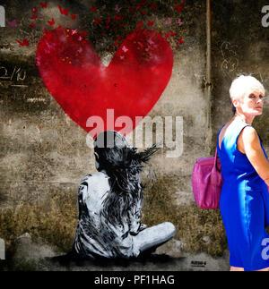 Arqua Petrarca, PD, Italien - 15 August, 2018, malte auf einer Wand in Arquà Petrarca. Ein kleines Mädchen von hinten gesehen und ein großes Herz im Hintergrund. Ein - Stockfoto