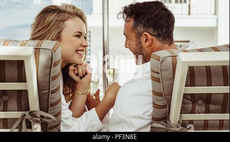 Romantisches Paar in bademänteln an einander mit einem Glas Wein in der Hand. Lächelnd Mann und Frau sitzen auf Liegestühlen im Freien. - Stockfoto