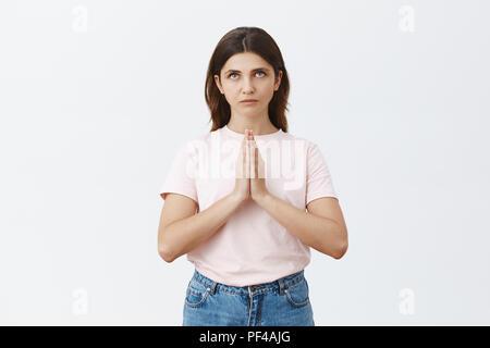 Innen- schuss von schweren fokussiert und treue Frau glauben an hod Glauben zu haben und hoffen, dass Gebete erhört, Hände halten, beten Sie mit strengen intensiven Ausdruck über grauer Hintergrund - Stockfoto