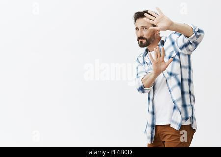 Angst vor Menschen, Angst bully wird ihn in Gesicht geschlagen, nach hinten neigen und zum Schutz von Punch mit erhobenen Händen und starrte Feind mit intensiven Ausdruck, Gefühl der Furcht vor grauem Hintergrund - Stockfoto