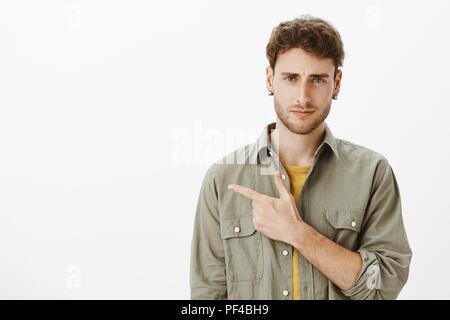 Guy Ausdruck der Ungläubigkeit, Nicht bereit, dorthin zu gehen. Portrait von unsicher, gut aussehendes männliches Modell mit Borsten in legere Kleidung und zeigte mit dem Zeigefinger und runzelte die Stirn, Ausdruck der Ungläubigkeit und Abneigung - Stockfoto