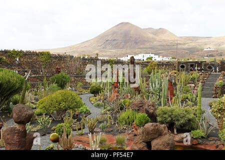 LANZAROTE, Spanien - 21 April, 2018: Tropische Kakteengarten Jardin de Cactus mit vulkanischen Bergen im Hintergrund, Guatiza Dorf, Lanzarote, Cana - Stockfoto