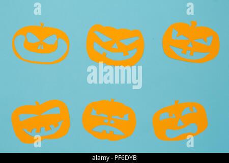 Halloween Hintergrund Einrichtung urlaub Konzept. Minimalismus flach auf Papier Ausschneiden von Jack O lustige Gesichter auf der blauen Tabelle Kürbis. - Stockfoto