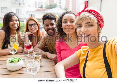 Selfie portrait. Freunde glücklich lächelnd und Sitzen im Cafe Bar im Freien. Mixed Race Gruppe Geselligkeit in einer Party im Restaurant außerhalb. Sommer, warme, f - Stockfoto