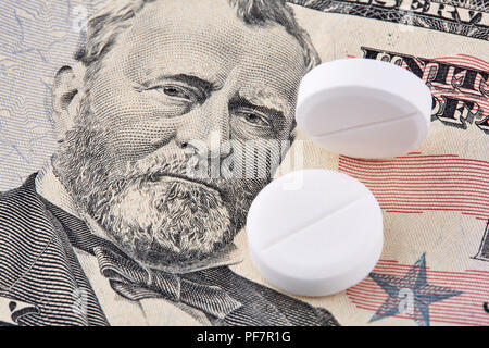 Zwei weiße Pillen liegen auf amerikanische Dollar Banknote. - Stockfoto