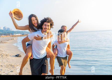 Eine Gruppe von Freunden zu Fuß am Strand entlang, mit Männer, piggyback Ride zu Freundinnen. Glückliche junge Freunde genießen Sie einen Tag am Strand