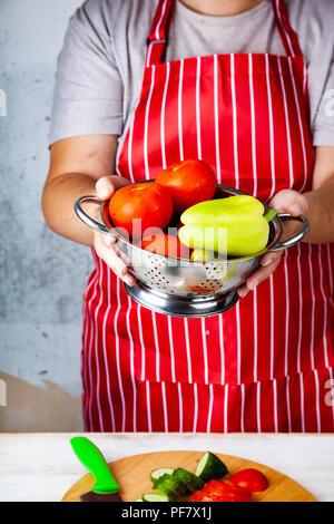 Frau in einem roten Schürze mit einem Sieb mit Gemüse für Salat. Das Kochen. - Stockfoto