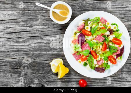 Shell pasta lecker Salat mit gemischte Salatblätter, Salami auf der weißen Schale mit Nüssen, Honig und Sesam Sauce, Nahaufnahme - Stockfoto